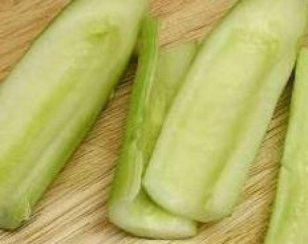 Peel cucumbers and removed seeds with a spoon. Grate cucumbers.