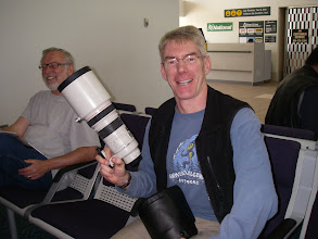 Photo: Awaiting our flight to Bella Bella, I pull out my mighty bear-shooting lens to show to a guest we just met (photo by Carolyn)