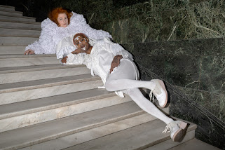 Photograph of me with short pink hair, wearing white lace facial decals, ornate ruffled and ruched white dress. Behind me is a similarly dressed pale skinned, ginger haired model. We are both lying on a marble staircase