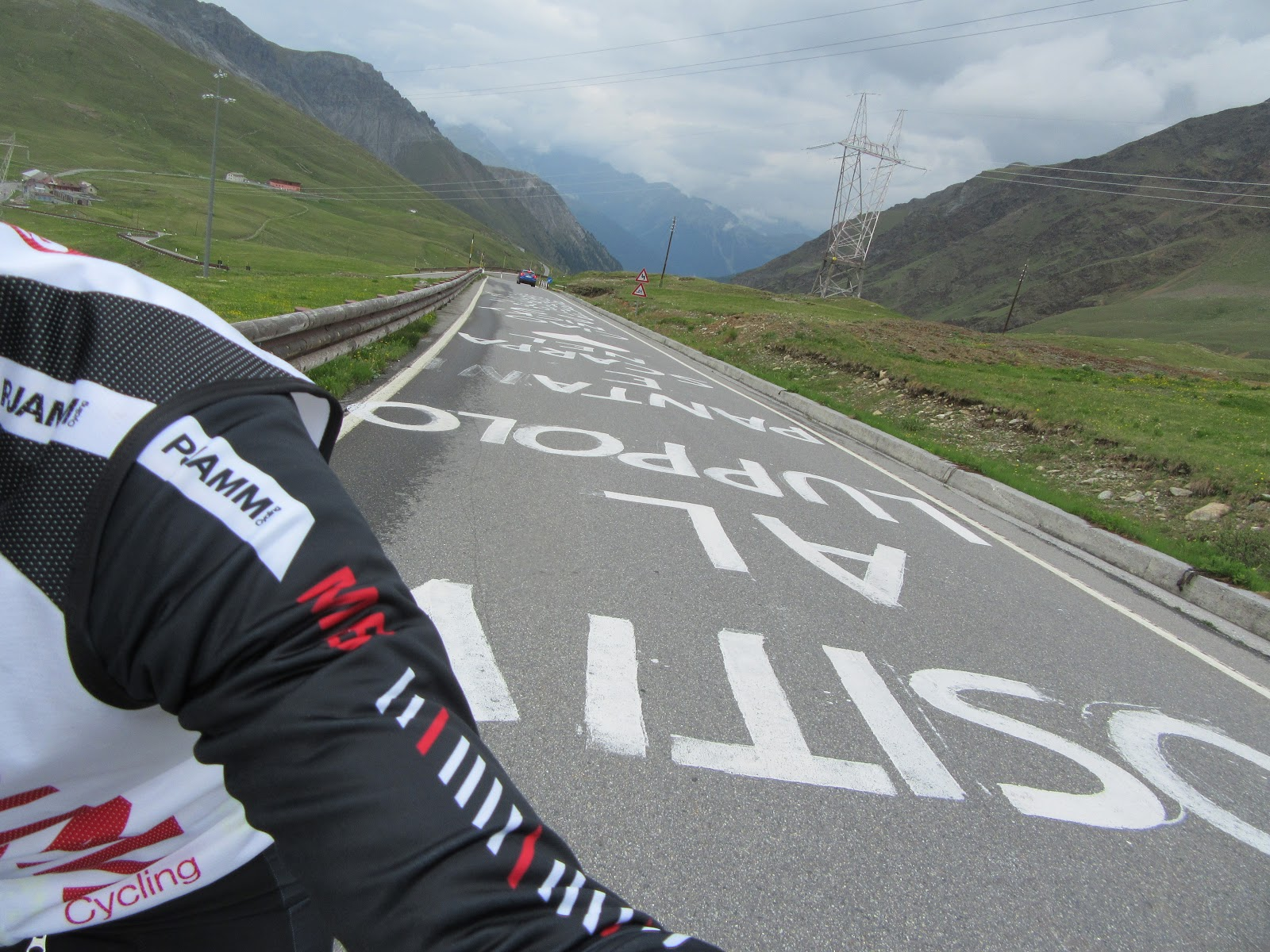 Climbing Umbrail Pass by bike to passo dello stelvio - giro d'italia signs painted on road, cyclist