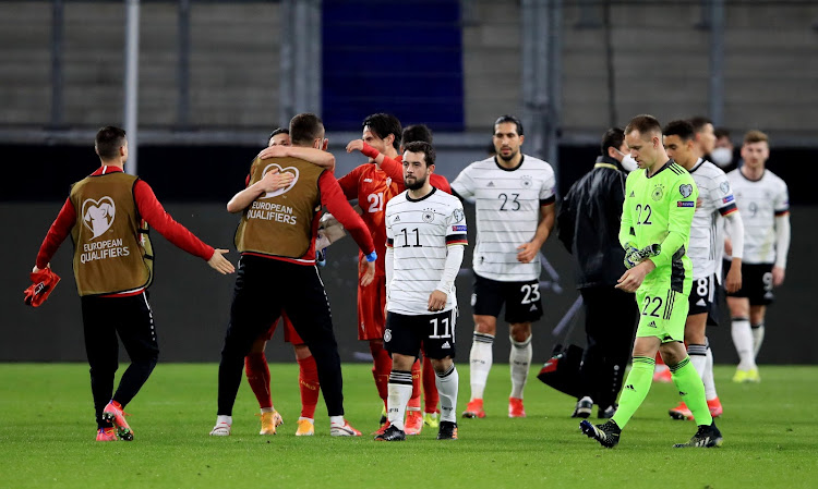 Germany players look dejected as the North Macedonia players celebrate after the match