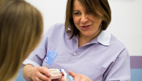 a dental hygienist talking to a patient