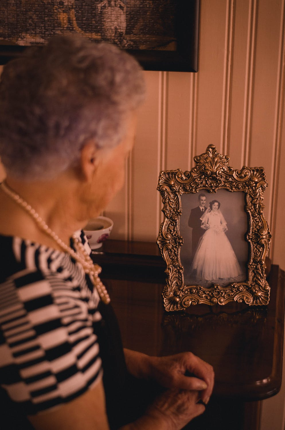 woman looking at a vintage marriage photo