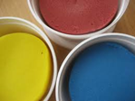 yellow, red, blue play dough in containers