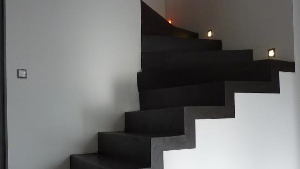 Les marches en béton ciré, encastrées dans le mur, les LED éclairent discrètement le paysage