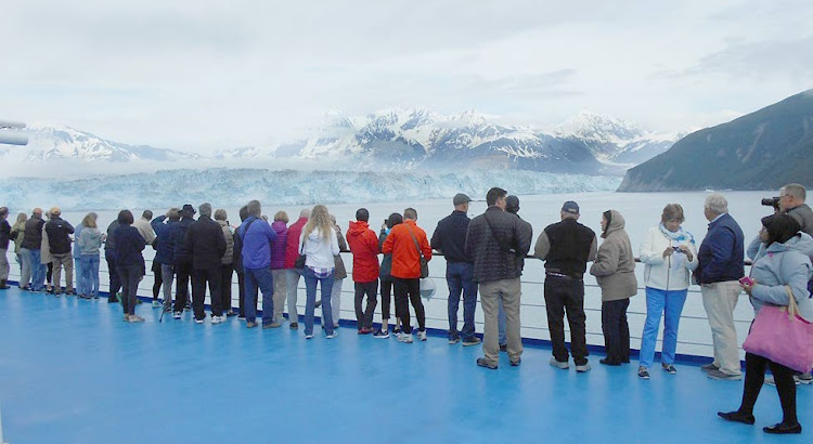 Passengers press against the rails to take in Hubbard Glacier.