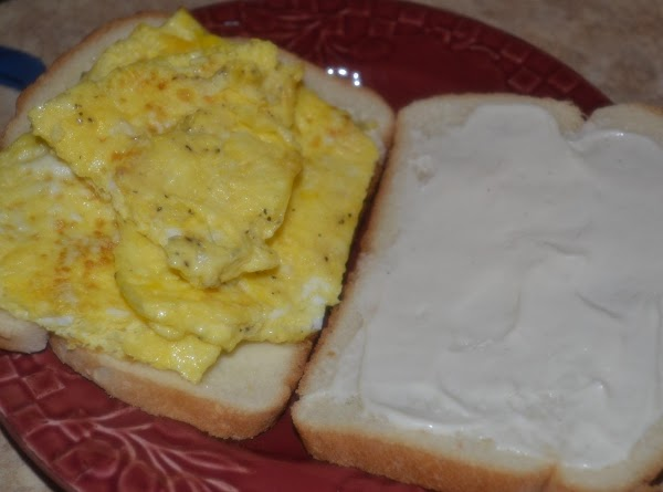 Cut omelet to fit bread slices.  Place omelet pieces on top of buttered...