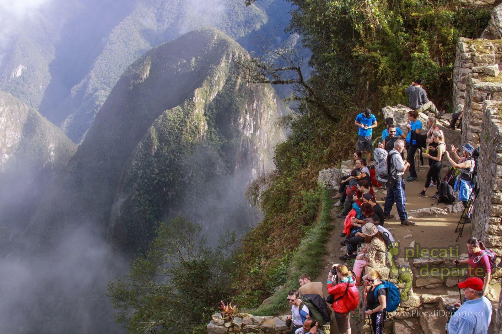 Turisti care fotografiaza cetatea Machu Picchu, de la Poarta Soarelui (Sun Gate), de pe Inca Trail