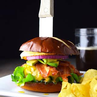 Bacon, Egg, and Avocado Cheese Burger on a Pretzel Bun.