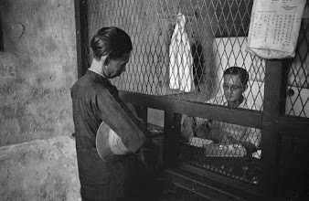 Photo: Photographer: Harrison Forman Singapore, man purchasing opium from another man behind cage, 1941