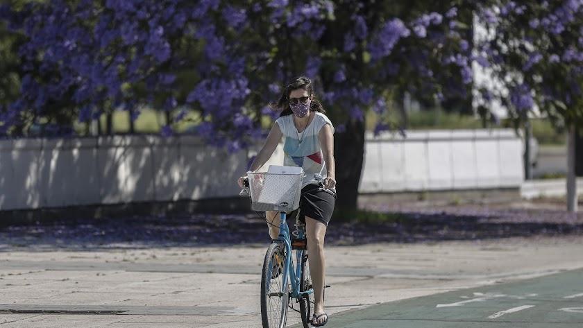 Una mujer con mascarilla pasea en bicicleta por el Puente del Alamillo, en Sevilla.
