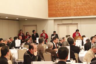 Photo: 懇親会の冒頭、功労賞受賞者発表の場面です。 奥野先輩、駒沢先輩は記念品授与係も兼務で前に待機中です!