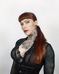 vrouw in zwarte jurk met uitbundige tatoeage op hals en boven haar decolleté