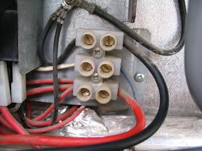 Photo: Desconecto la conexión de 12 voltios. El rojo es el positivo que viene del repartidor de carga, el negro el negativo y el azul es la señal D+ del alternador. Según voy quitando los cables los voy encintando para evitar un contacto.