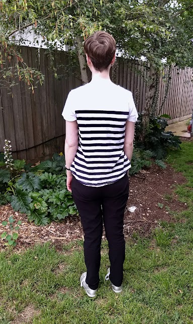 Siobhan stands in front of a garden fence. She wears slim fit black pants with hard-to-notice front pockets, striped white and navy short sleeve tee and silver runners. Her back is to the camera.