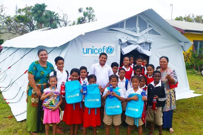 School children and teachers stand outside a make-shift tent school