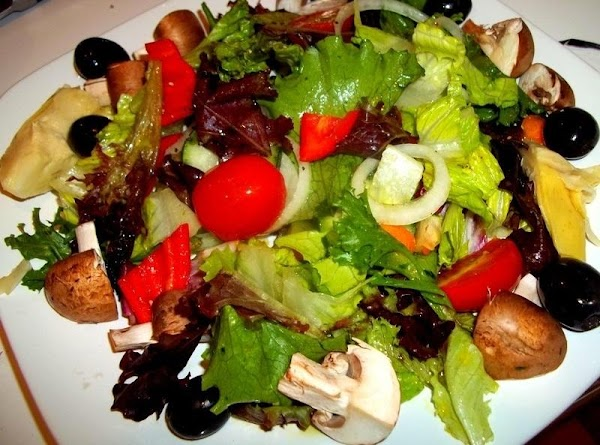 Divide the mixed greens between 2 plates. If using artichokes, olives...mushrooms, place then around...