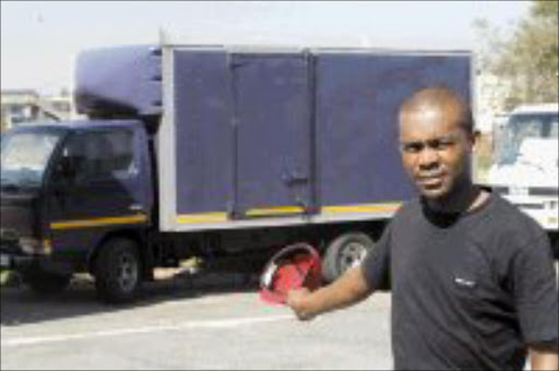 WHEELER DEALER: Thabo points to the unreliable and joined truck his sister Sini Pooe bought from Wall Street Projects. Pic. Antonio Muchave. © Sowetan.