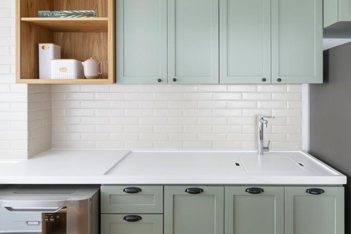 cozinha com bancada da pia branca, parede da pia com revestimento subway tiles branco, armários cinza claro e detalhes amadeirado.