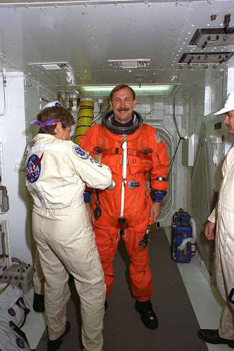 Commander Curtis L. Brown is assisted as he prepares to enter the Space Shuttle orbiter Discovery at Launch Pad 39A.
