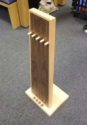 a monolith shaped cue rack on a grey carpet