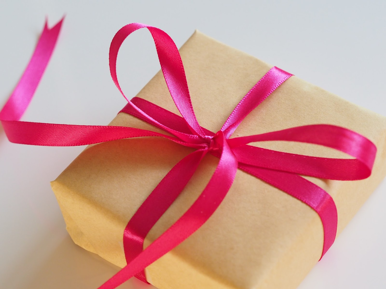 A package covered in brown paper with a hot pink decorative ribbon