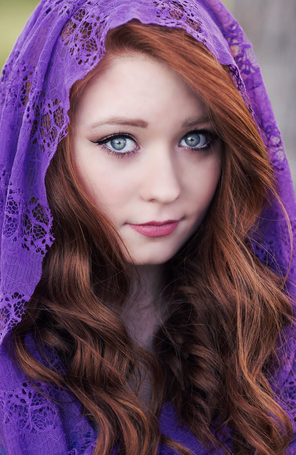girl with red hair wearing a purple head covering