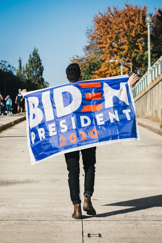 Biden supporter walking with a Biden banner in Washington.