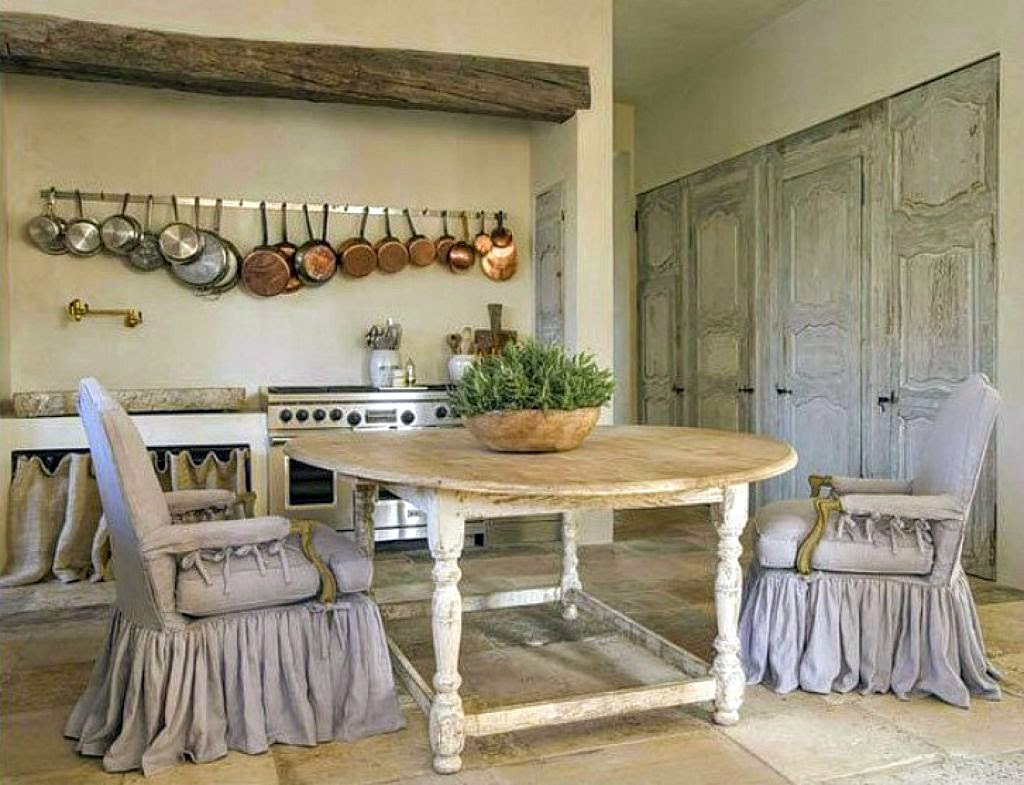 Stunning French Country kitchen designed by Pamela Pierce with antique table, slipcovered chairs,, rustic beam over range, and copper pots. #frenchcountry #frenchkitchen #pamelapierce
