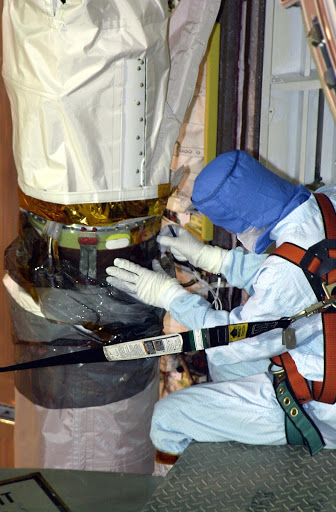 One of a team of robotic experts looks at the site of the scrape on the surface of the the robotic arm's honeycomb shell.