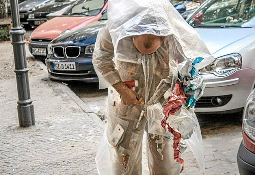 A still from the video performance of Kai Lossgott in his 'Hunter-gatherer' suit, collecting urban detritus for future categorisation.