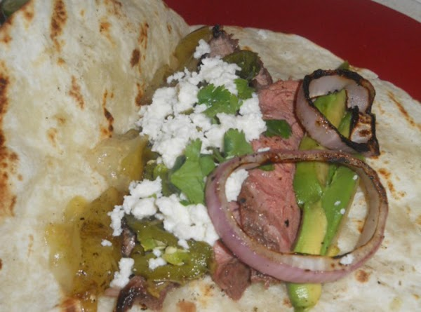 Assemble tacos by layering onto a grilled tortilla; 2-3 slices of steak, a ring...