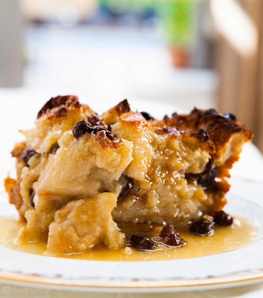 A  piece of bread pudding covered in bourbon sauce served on a plate