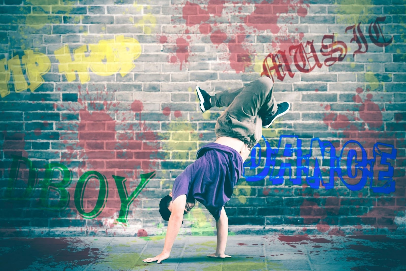 A person break dancing in front of a wall covered in graffiti