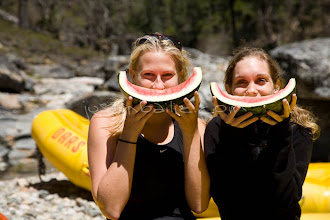"""Photo: Two young women """"smiling"""" with watermelon slices while whitewater rafting on the Stanislaus River, CA."""
