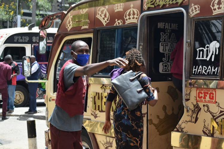 A conductor at the ROG Sacco matatu stage guides passengers into a bus on April 4, 2020.