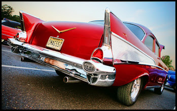 """Photo: A 1957 Chevrolet sporting in tail fins.  per 57classicchevy.com:   """"The 1957 Chevrolet received major restyling and some important engineering upgrades, including a big boost in horsepower. The new styling was the finest of the 1955-57 """"Classic Chevy's"""". Chevy advertised it's '57 as """"Sweet, Smooth and Sassy! Chevy goes one better for '57 with a daring new departure in design (looks longer and lower, and it is!), exclusive new Turboglide automatic transmission with triple turbines, a new V-8 and a bumper crop of new ideas including fuel injection!"""" said one ad. """"You'll love Chevrolet's new light-touch driving! You'll never put hand and foot to a car so quick, smooth and easy to control - a light touch does it, Chevy's solid on the road - and that goes for the way it's put together, too!"""" said another.The 1957 Chevrolet was smaller than the competition so the styling was deliberately fashioned to make it look as large as possible and it had the boldest and biggest look among low priced cars. The massive new bumper and grille is just one example. Front fenders were stretched across the top of the head lights and the unique and distinct rear fins, that all 1957 Chevy fans love, helped to make the car look much larger and lower."""""""