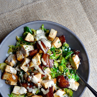 "Warm Brussels Sprouts Caesar Salad with Chicken and Crispy Bacon ""Croutons""."