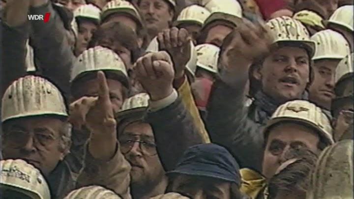 Protestdemo: Arbeiter mit Schutzhelmen, erhobene Fäuste.