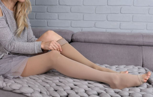 skin tone compression socks is put on by a pregnant woman in the morning
