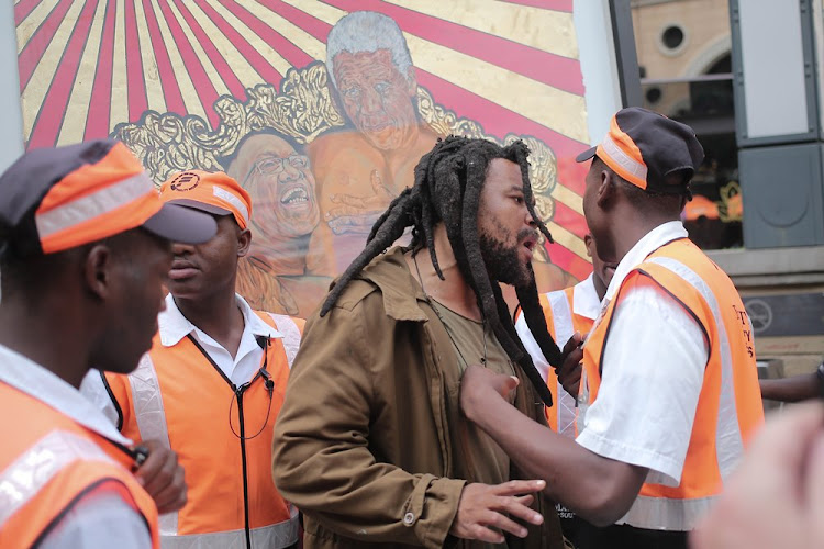 Controversial Artist Ayanda Mabulu argues with security at Sandton Square in Johannesburg after erecting one of his artworks showing President Jacob Zuma and Nelson Mandela in the shopping centre.