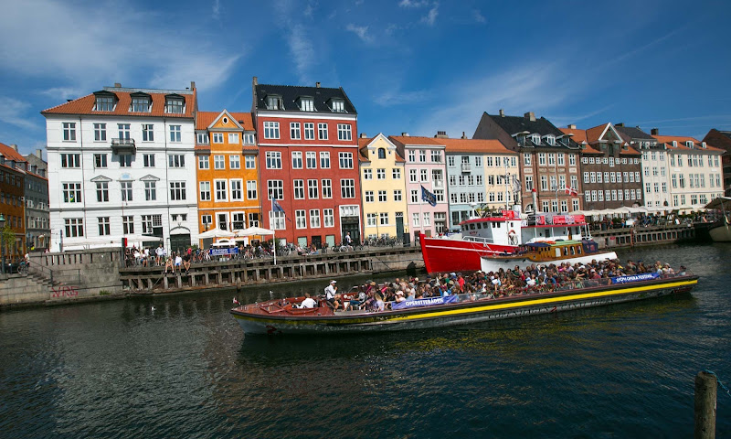 A tour boat plies a canal in the Nyhavn neighborhood of Copenhagen, Denmark.