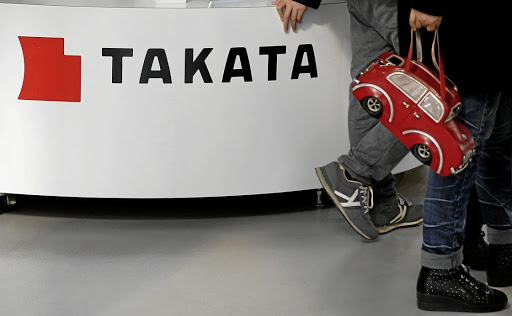 Visitors walk past a Takata logo on display at a vehicle showroom in Tokyo, Japan. Picture: REUTERS