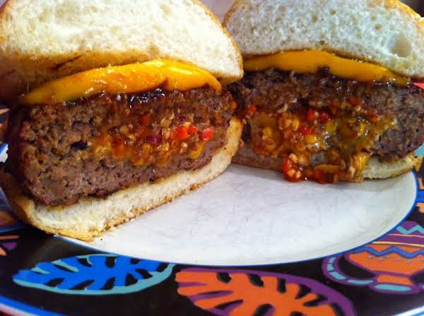 Burger Halves Stuffed With Melted Cheddar Cheese On A Bun.