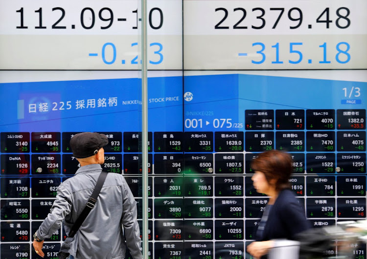 People walk past an electronic board showing Japan's Nikkei average, top right, and the yen's exchange rate against the dollar outside a brokerage in Tokyo. Picture: REUTERS/TORU HANAI/FILE PHOTO
