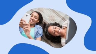 una mujer y una niña tumbadas mirando un smartphone y un tablet