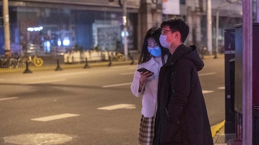Una pareja con máscaras por el coronavirus en Shangai.