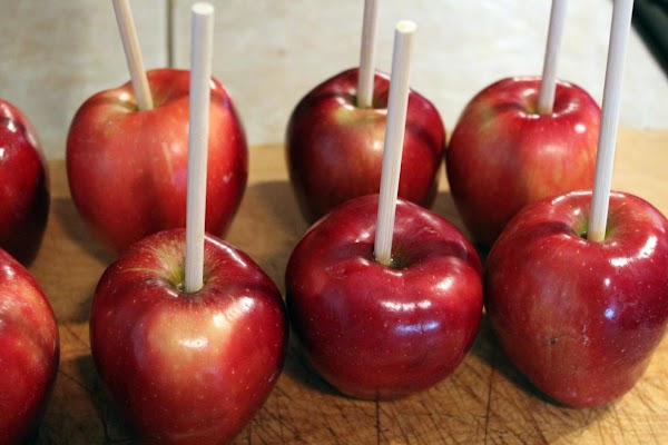 Popsicle sticks placed inside red apples.