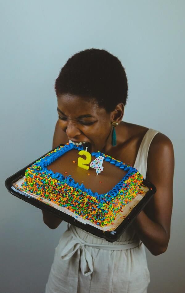 foto de uma mulher negra segurando e abocanhando um bolo
