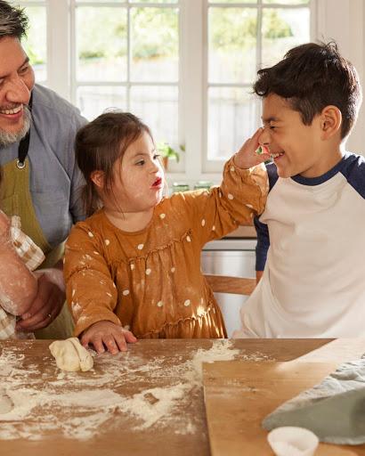 Die Tochter und ihr älterer Bruder spielen mit Zutaten, während der Vater lächelnd zusieht.